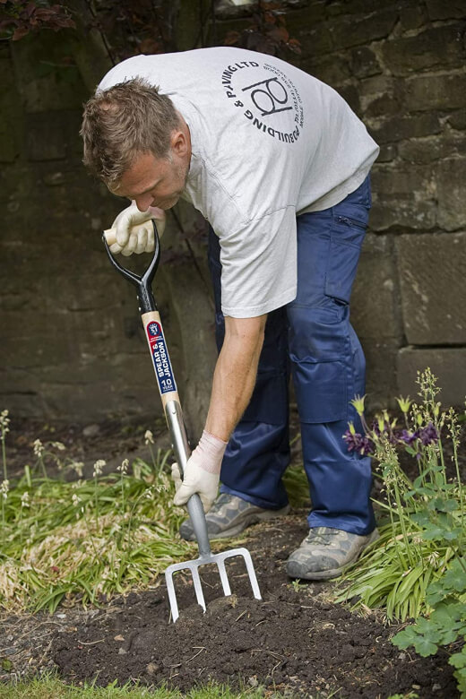 a man digging with a garden fork