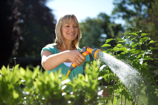 a woman watering her garden with a hose nozzle sprayer