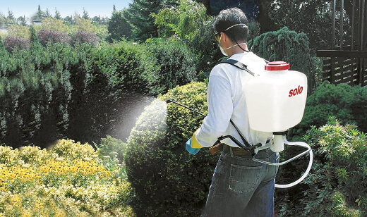 A man using a backpack sprayer with ease.