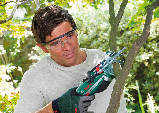 A man using a Bosch cordless garden saw