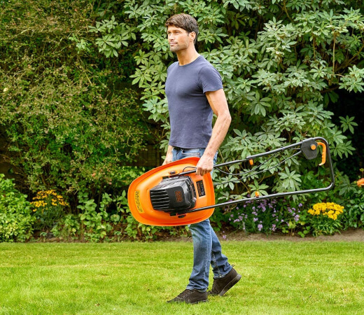 a man carrying an electric lawn mower