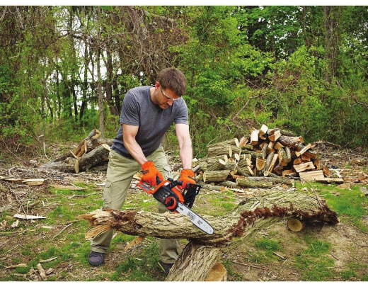 A man using an electric chainsaw