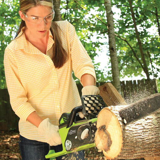 A woman using an electric chainsaw
