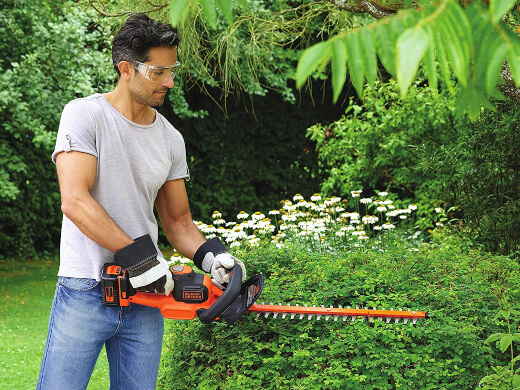 A man using a hedge trimmer